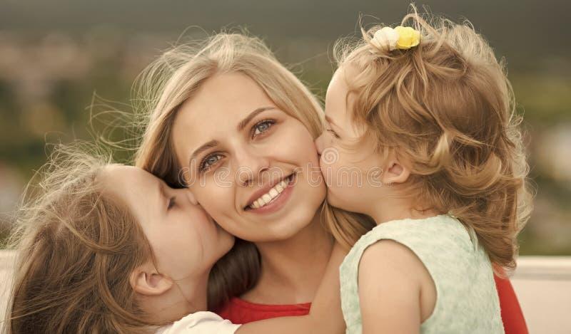 Dia de matrizes Mãe do beijo das filhas na paisagem natural imagens de stock royalty free