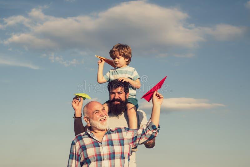 Dia de pais - o avô, o pai e o filho estão abraçando e estão tendo o divertimento junto Avi?o pronto para voar Retrato de feliz fotografia de stock royalty free