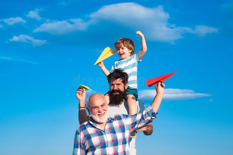 Dia de pais - o avô, o pai e o filho estão abraçando e estão tendo o divertimento junto Conceito da inf?ncia Multi geração mascul imagens de stock