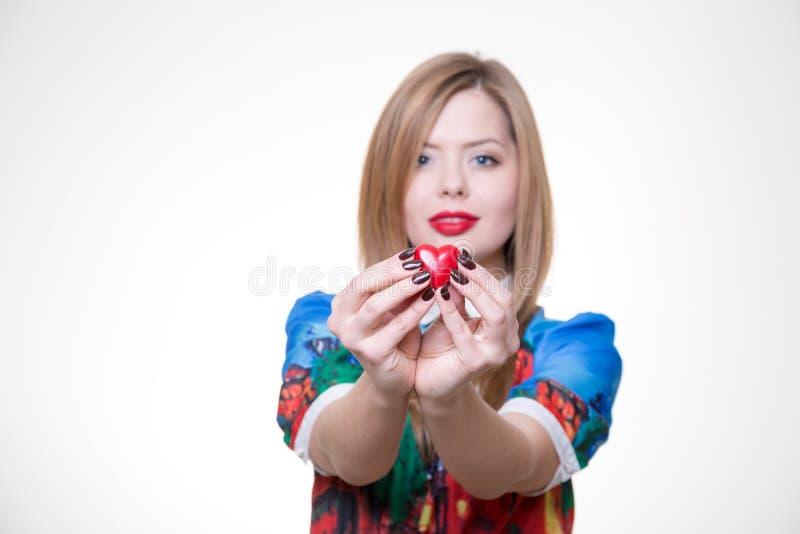 Dia de são valentim feliz com o louro bonito que guarda o coração vermelho imagem de stock