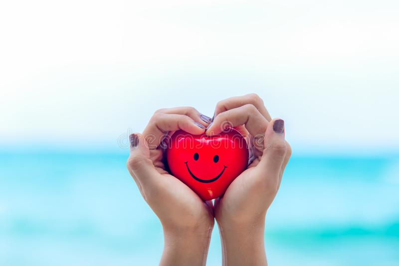 Dia de são valentim, forma vermelha do coração do sorriso da terra arrendada da mulher da mão na praia, imagem de stock