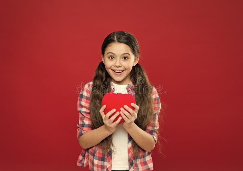 Dia de sa?de de mundo Menina que guarda o cora??o vermelho grande Pouco crian?a que expressa o amor no dia de Valentim Menina bon foto de stock