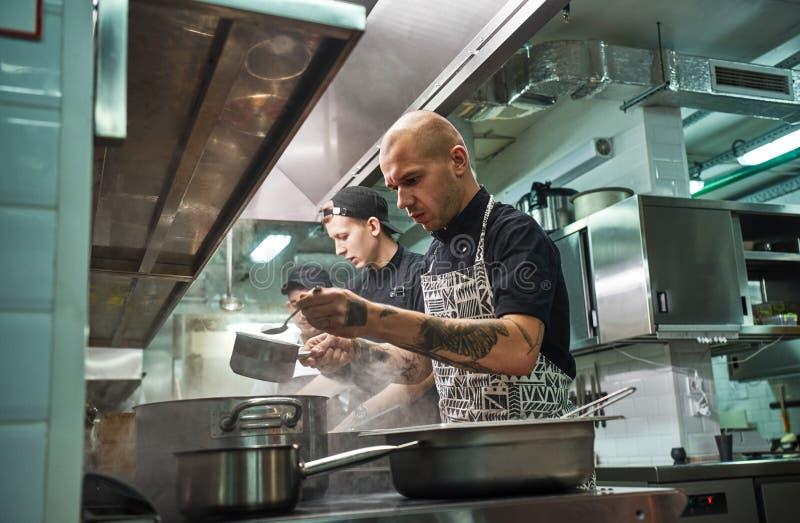Dia de trabalho ocupado Equipe profissional do cozinheiro chefe do restaurante e seus dois assistentes novos que cozinham na cozi imagens de stock
