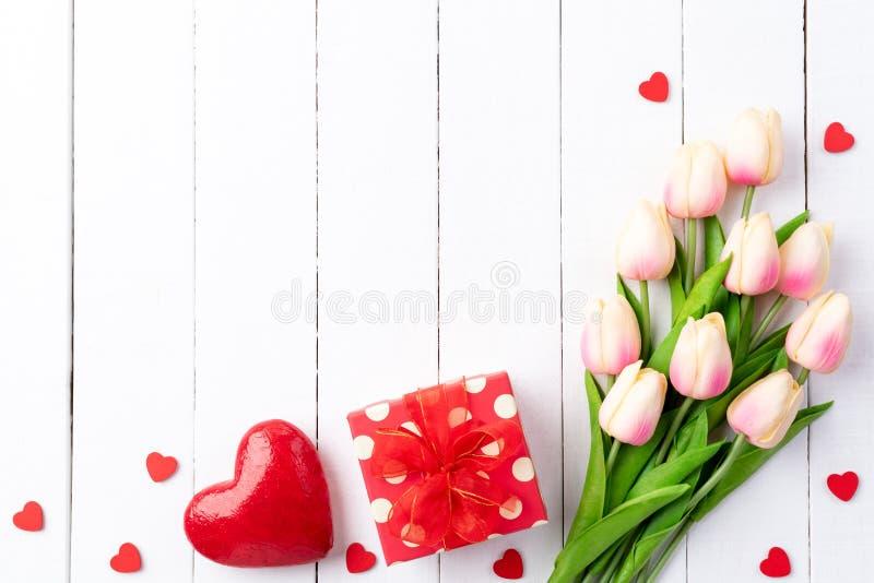 Dia de Valentim e conceito do amor Dois corações vermelhos feitos a mão com tulipas e caixa de presente em de madeira branco imagens de stock