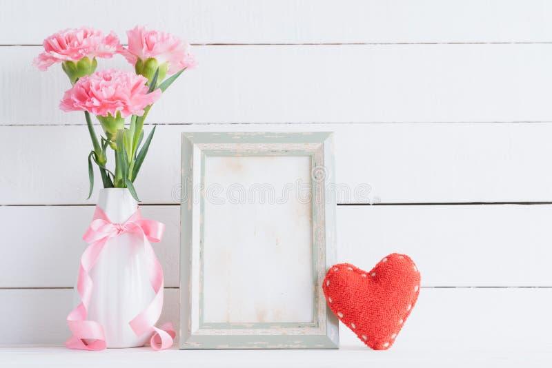 Dia de Valentim e conceito do amor Flor cor-de-rosa do cravo no vaso com moldura para retrato velha do vintage e coração vermelho fotos de stock royalty free