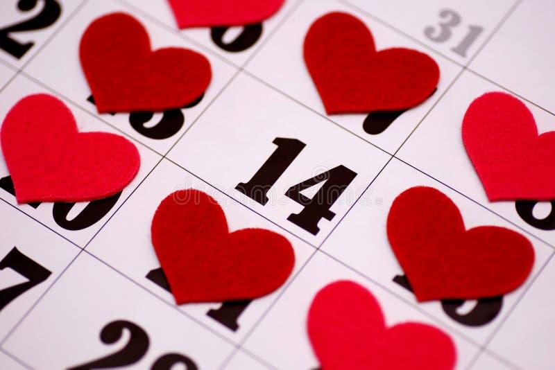 Dia de Valentim e conceito dos feriados - feche acima da folha do calendário com a data do 14 de fevereiro marcada pela forma ver imagem de stock