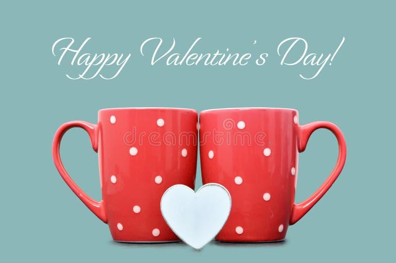 Dia de Valentim feliz: Duas canecas vermelhas e coração de madeira imagem de stock royalty free