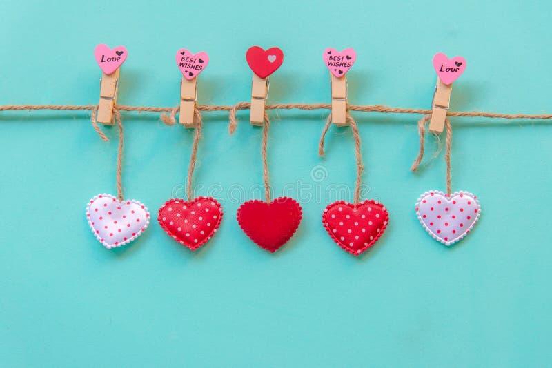 Dia de Valentineâs Os corações costurados do descanso enfileiram a beira em pregadores de roupa vermelhos, cor-de-rosa e brancos  imagem de stock