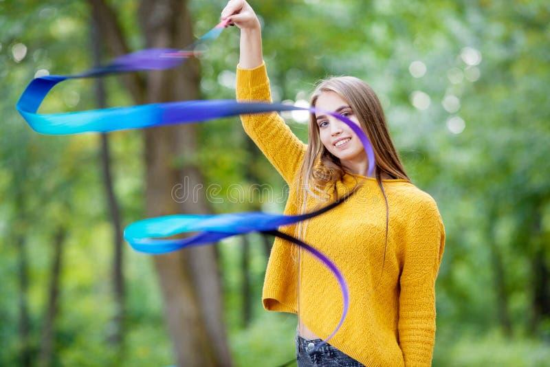 Dia de verão bonito da menina com uma ginástica da fita azul imagem de stock