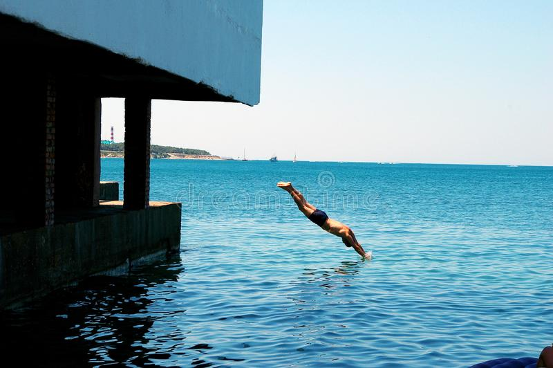 Dia de verão no mar, mergulhos de um homem do cais no mar foto de stock
