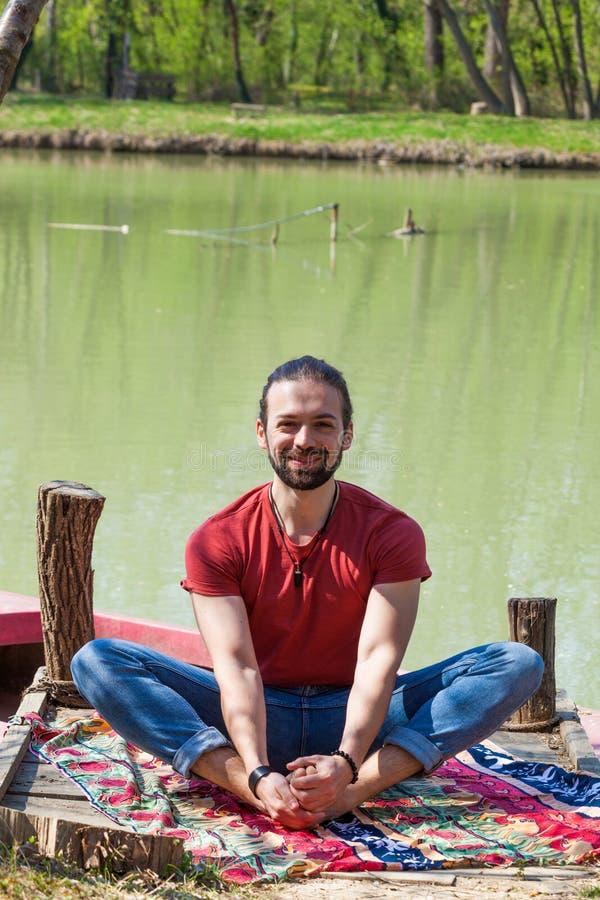 Dia de verão de sorriso da ioga da prática do homem novo pela pose do lago para esticar os quadris imagens de stock
