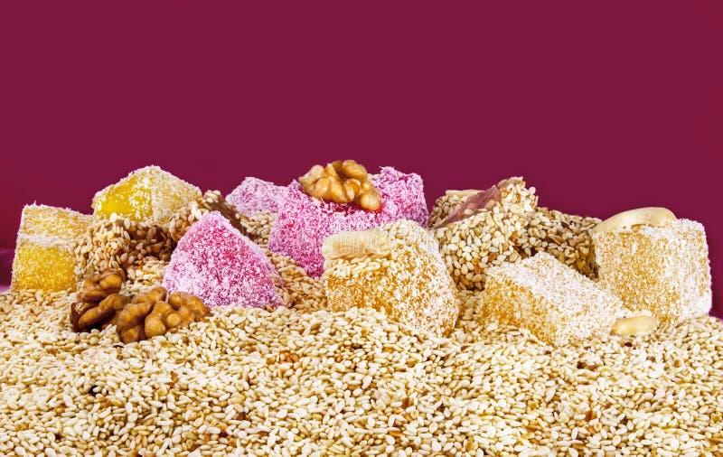 Dia der türkischen Freude mit Nüssen und indischem Sesam auf einem rosa Hintergrund, Nahaufnahme stockbilder