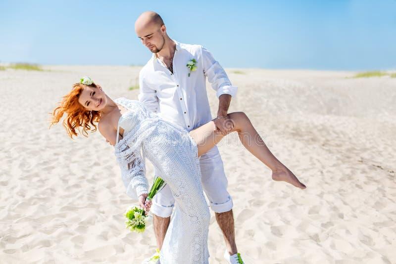 Dia do casamento Pares novos felizes no amor Noiva e noivo na praia imagem de stock