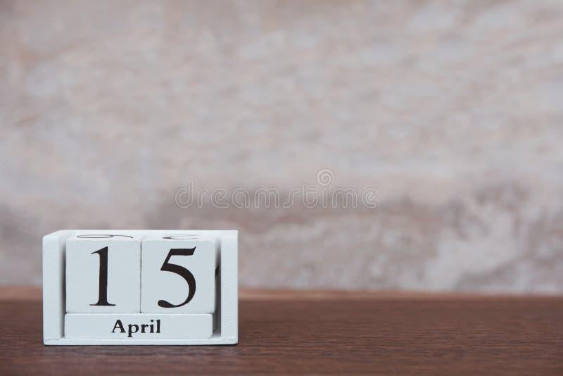 Dia do imposto com o 15 de abril Cubo de madeira do bloco do calendário com número No fundo de madeira da prancha escura da tabel fotos de stock