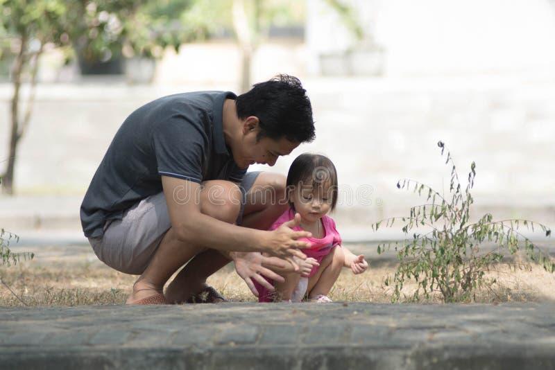 Dia do pai feliz - homem e sua filha que jogam no parque com a menina que mostra algo a seu pai no dia ensolarado fotografia de stock