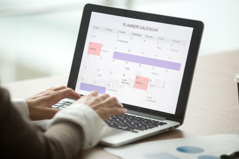 Dia do planeamento da mulher de negócios usando o calendário digital no portátil, clo imagem de stock