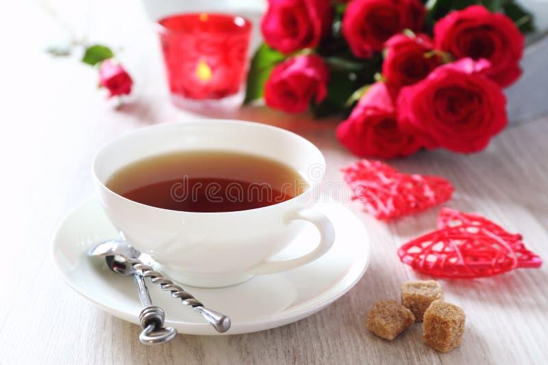 Dia do ` s do Valentim: Bebida romântica do chá com vela e as rosas vermelhas fotografia de stock