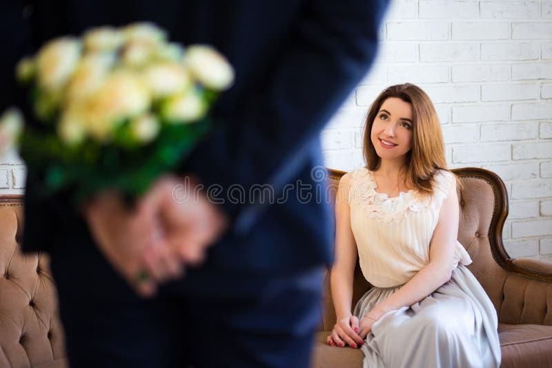 Dia do ` s do Valentim ou conceito do aniversário - equipe flores escondendo de foto de stock