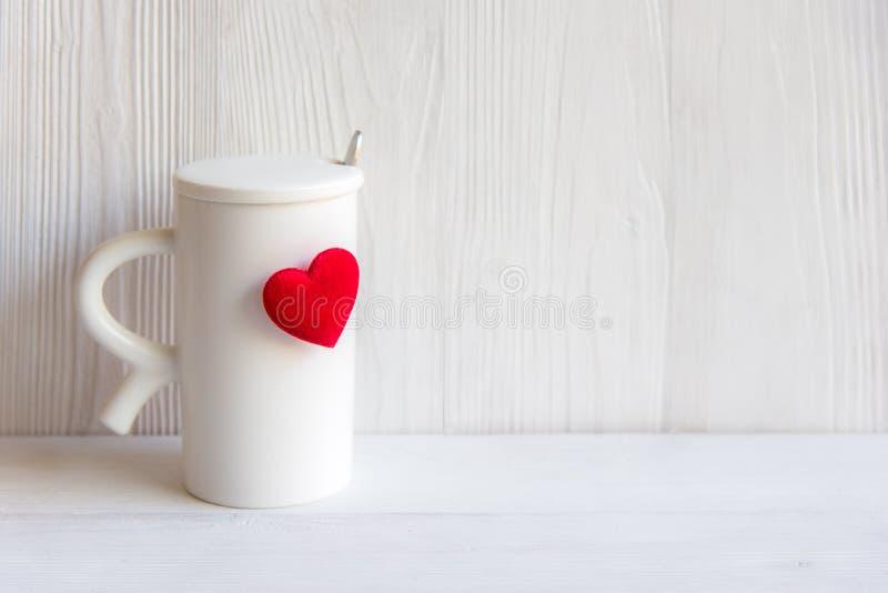 Dia do ` s do Valentim com coração vermelho no copo, fundo branco de madeira do café branco do copo foto de stock royalty free