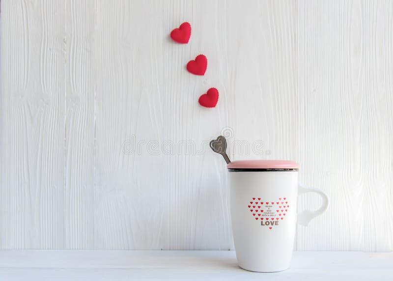 Dia do ` s do Valentim com fileira vermelha do coração do café branco do copo no copo, fotografia de stock royalty free