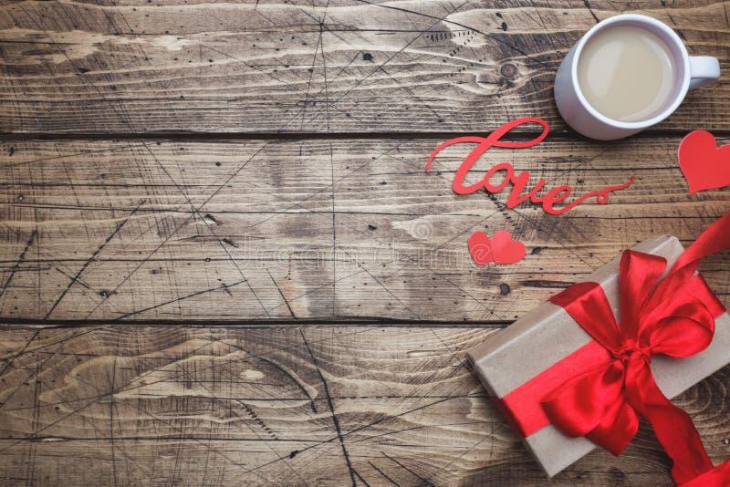 dia do ` s do Valentim do conceito Caixa de presente com curva vermelha e xícara de café na tabela de madeira Copie o espaço imagem de stock royalty free