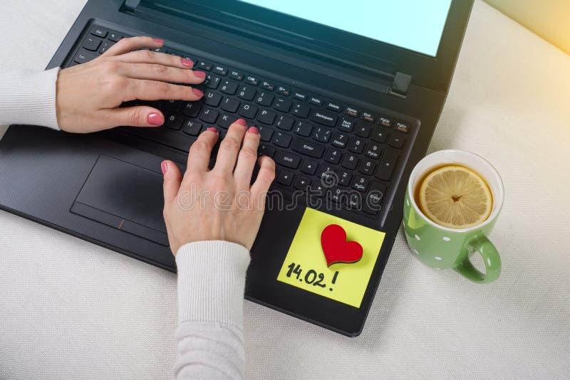 Dia do `s do Valentim nota do texto 14 02 escritos em uma etiqueta de papel Computador do fundo, portátil, mãos do ` s da mulher  fotos de stock royalty free