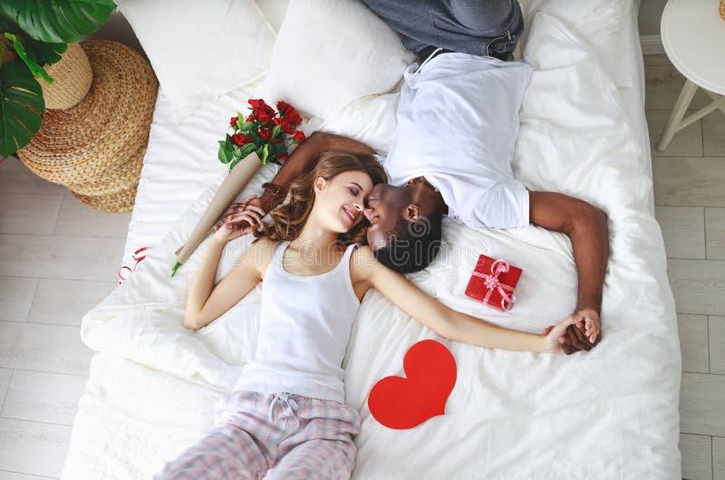 Dia do `s do Valentim pares felizes com as flores na cama foto de stock