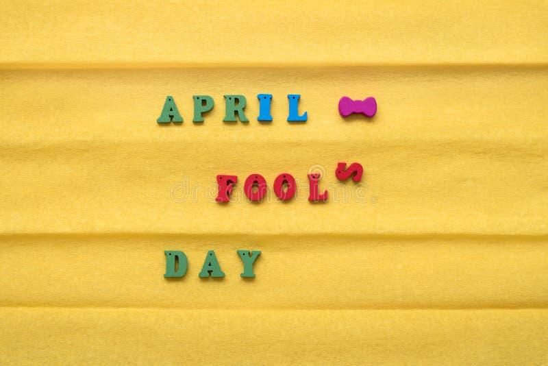 Dia do dia do tolo, inscrição das letras multi-coloridas em um fundo de papel amarelo imagens de stock