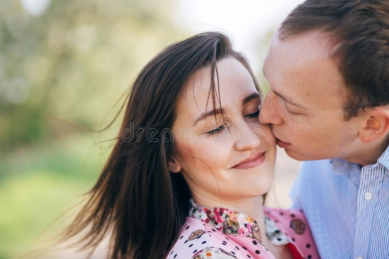 Dia do Valentim Aperto sensual dos pares novos bonitos e beijo na estrada na luz do sol entre o campo e as árvores da mola Famíli imagem de stock