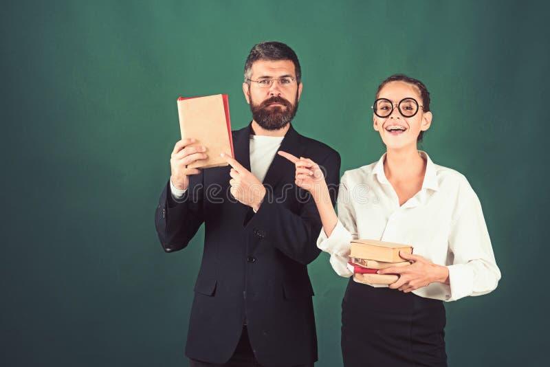 Dia dos professores com o homem e a jovem mulher que guardam e que apontam o dedo nos livros que apresentam o produto, espaço da fotos de stock royalty free