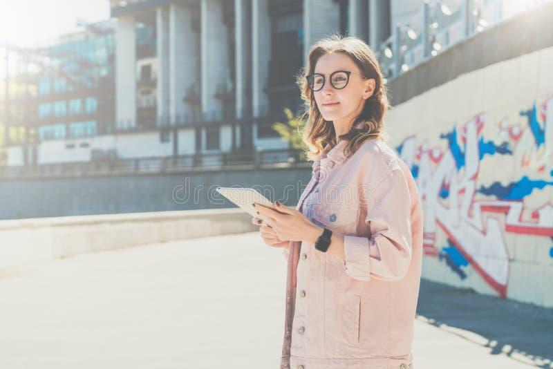 Dia ensolarado do verão A mulher nova do moderno nos vidros está na rua da cidade e usa o tablet pc fotografia de stock