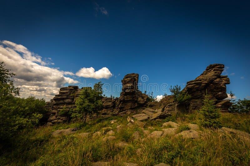 Dia ensolarado em Obri skaly sob o pico Serak em Jeseniky com o pinheiro da grama verde e escuro - céu nebuloso azul imagens de stock