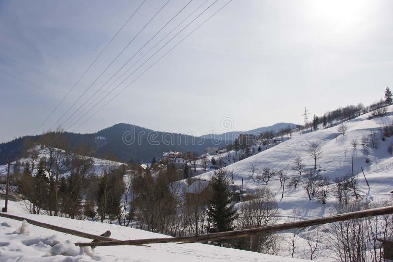 Dia ensolarado, vista da janela em uma paisagem nevado do inverno Aldeia da montanha, casas e cercas fotos de stock royalty free