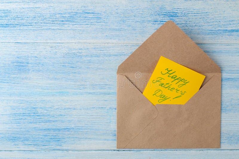 Dia feliz do ` s do pai Texto em um envelope em um claro - fundo de madeira azul Vista superior foto de stock royalty free