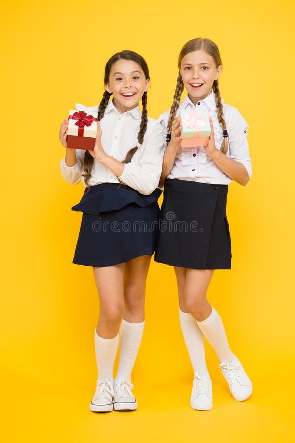 Dia grande da compra Presentes felizes da compra das meninas na venda no fundo amarelo Crianças de sorriso com presentes de papel foto de stock