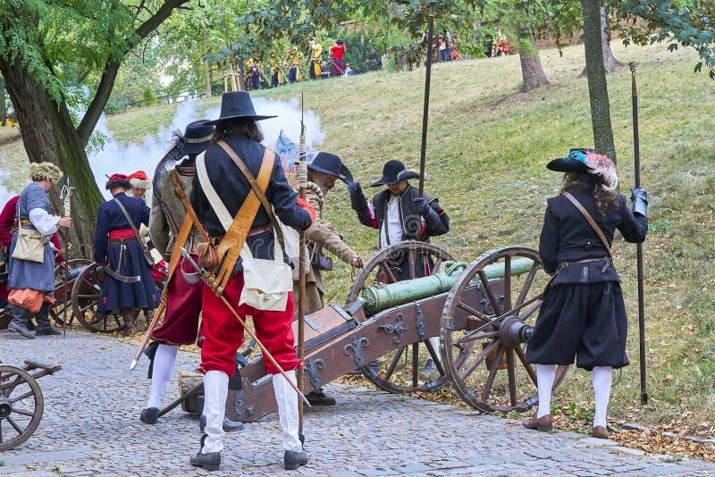 Dia histórico do reenactment de Brno Os atores em trajes históricos da infantaria recarregam mosquetes antes do ataque novo fotos de stock royalty free