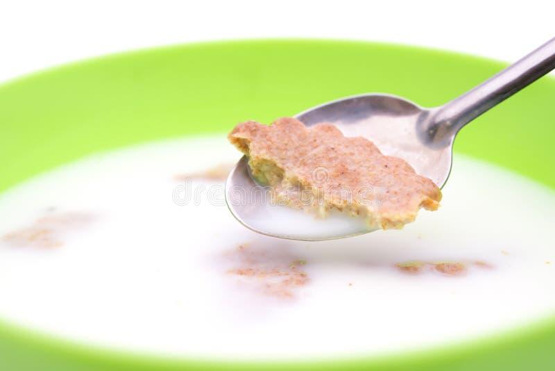 Dia la presa a cucchiaiate del cracker fuori d'inzuppamento dalla ciotola di latte con il clippi fotografia stock