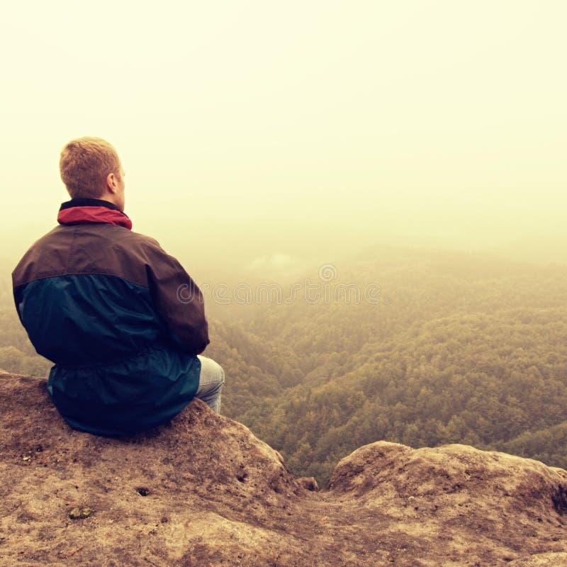 Dia melancólico e triste Homem no enge da rocha acima de profundamente vally Turista no pico da rocha do arenito que olha à névoa imagens de stock royalty free