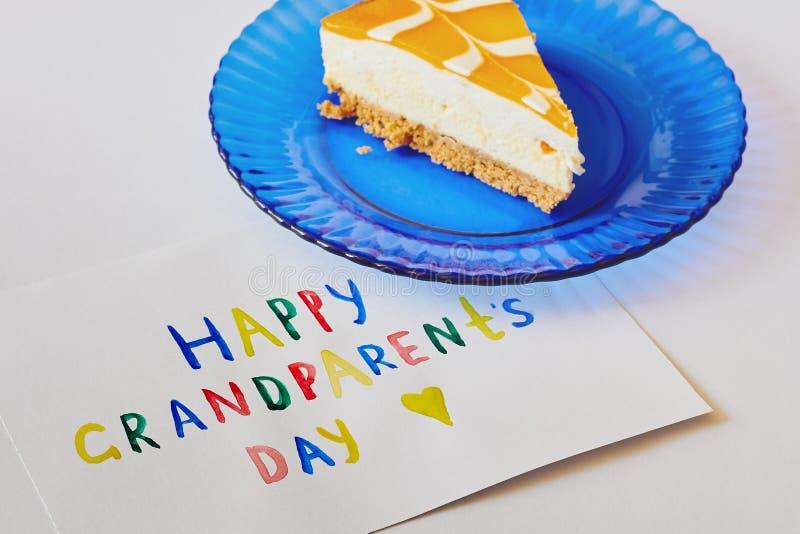 Dia nacional feliz das avós Cartão colorido feito por crianças e por pedaço de bolo na placa azul como o presente fotografia de stock