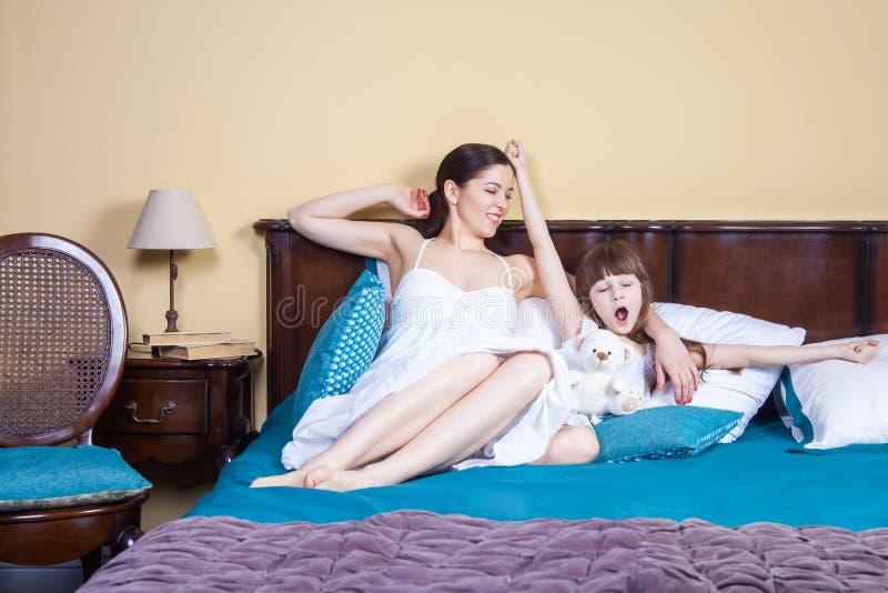 Dia novo do bom dia! A mamã e a criança acordam, as mãos acima, stretchin fotografia de stock royalty free