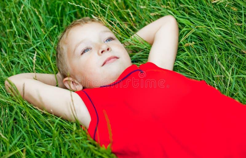 Dia pensativo da criança que sonha na grama fresca imagem de stock