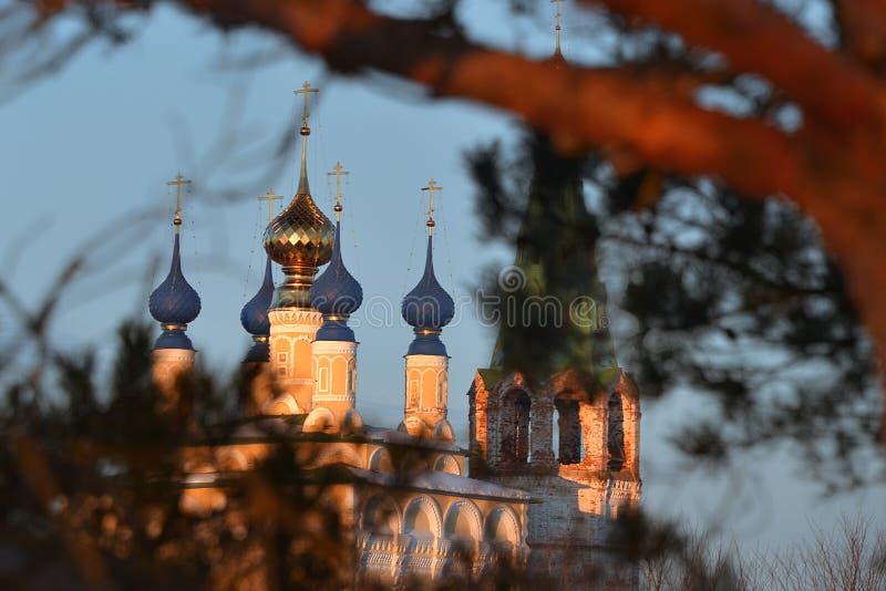 Dia velho do céu da igreja e das árvores da rua da vila de Dunilovo foto de stock