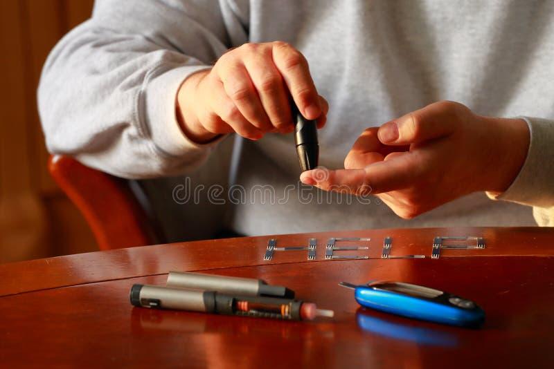 diabète Mètre de glucose de sang Niveau de mesure de sucre d'homme adulte dans le sang à la table image libre de droits