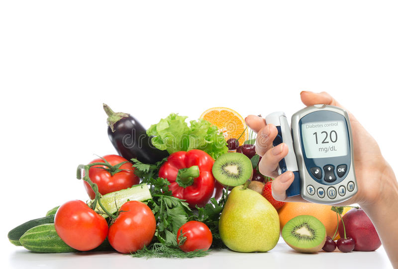 Diabetes concept glucose meter fruits and vegetables. Diabetes concept glucose meter in hand and healthy organic food fruits and vegetables organic green apple stock photography