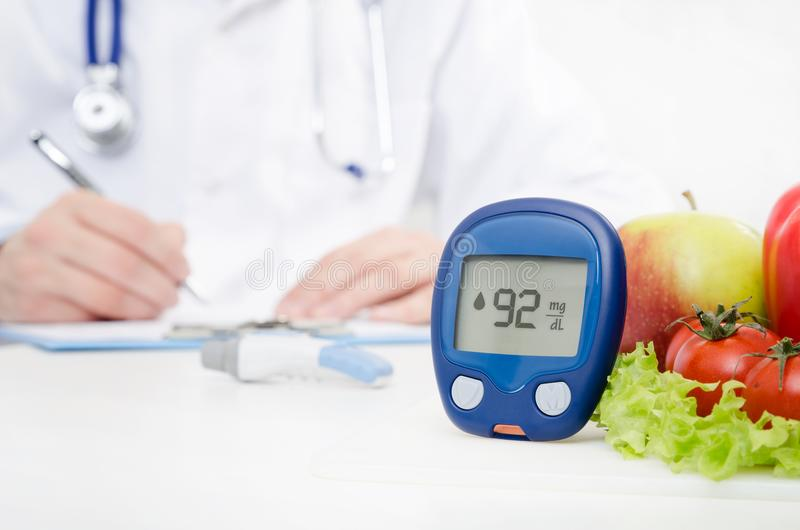 Diabetes at the doctor. Glucometer and vegetables concept stock image