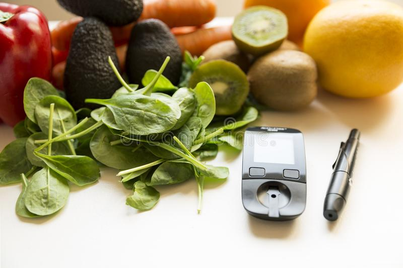 Diabetes monitor, diet and healthy food eating nutritional concept with clean fruits and vegetables with diabetic measuring tool royalty free stock photos