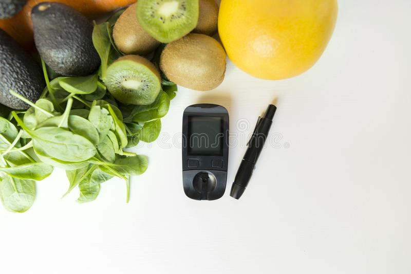 Diabetes monitor, diet and healthy food eating nutritional concept with clean fruits and vegetables with diabetic measuring tool stock images