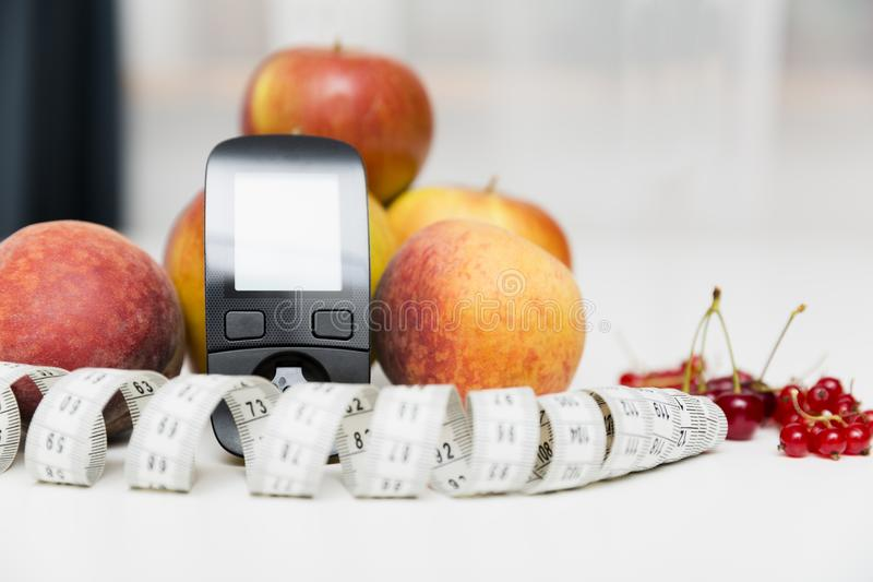 Diabetes monitor, diet and healthy food eating nutritional concept with clean fruits with diabetic measuring tool kit ans stock image