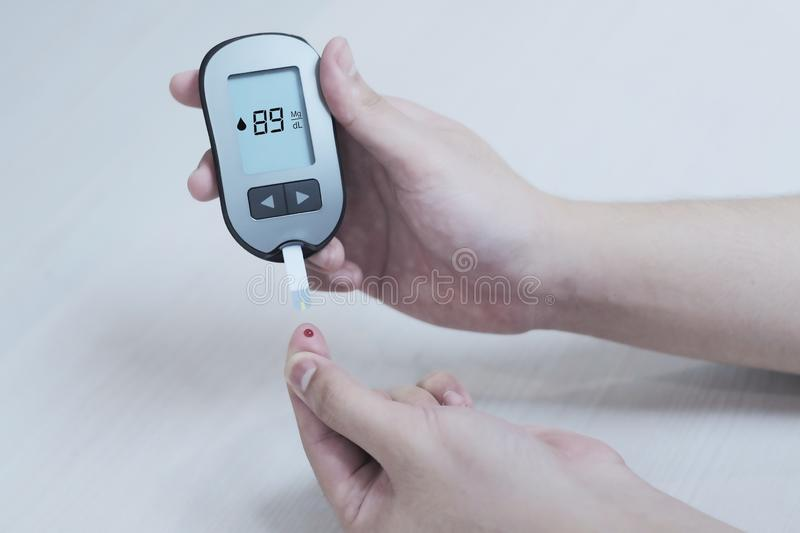 Diabetes patients use a sugar glucose meter to measure their blood glucose levels at home. Medical, test, diabetic, care, insulin, person, health, disease royalty free stock photography