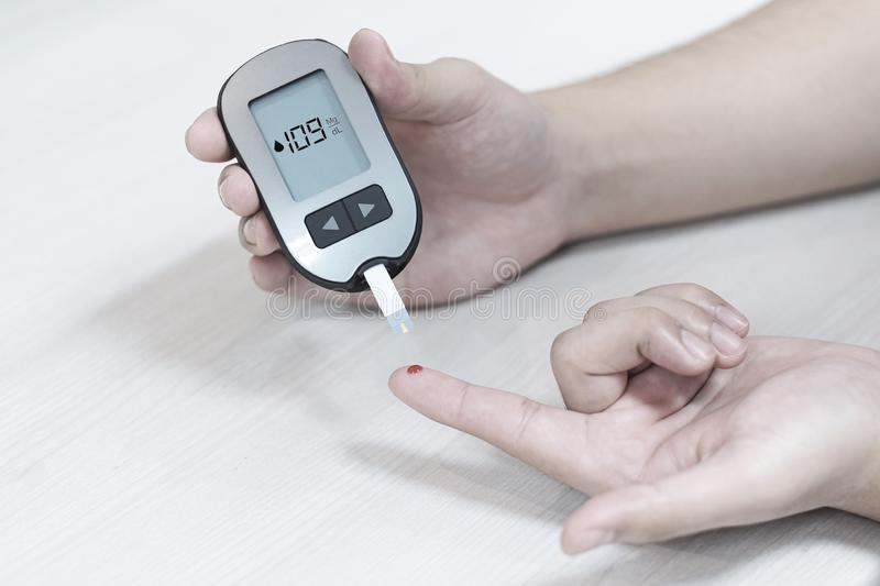 Diabetes patients use a sugar glucose meter to measure their blood glucose levels at home. Medical, test, diabetic, care, insulin, person, health, disease royalty free stock images